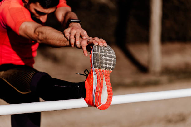 unrecognizable young runner man athlete stretching at the race track. Sports outdoors stock photo