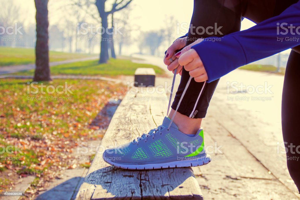 Unrecognizable young runner tying her shoelaces stock photo
