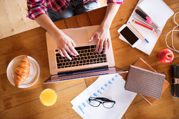 Unrecognizable young woman at home, working on laptop, studying stock photo