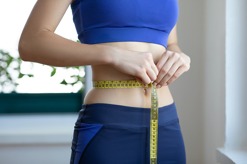 Unrecognizable young woman measuring her waist