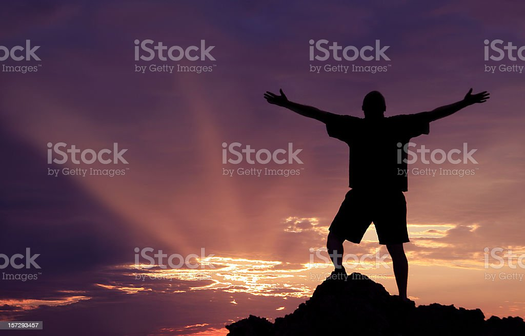 Unrecognizble Man Lifting His Arms in Worship stock photo