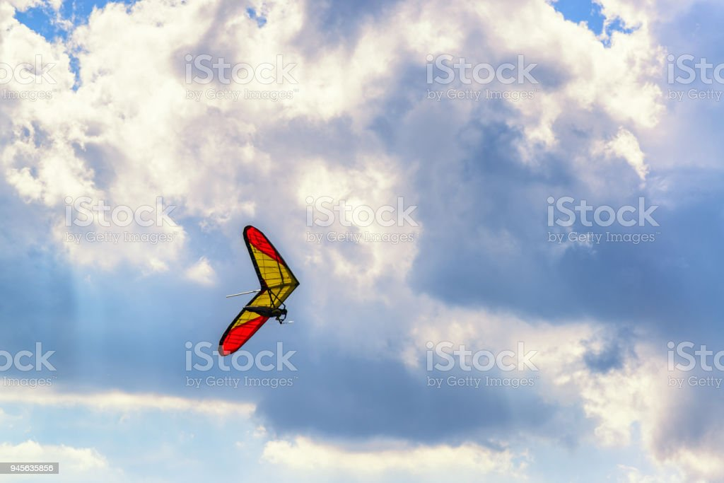 Unrecognized brave extreme hangglider pilot flies on a hang glider with deep blue sky and clouds above stock photo