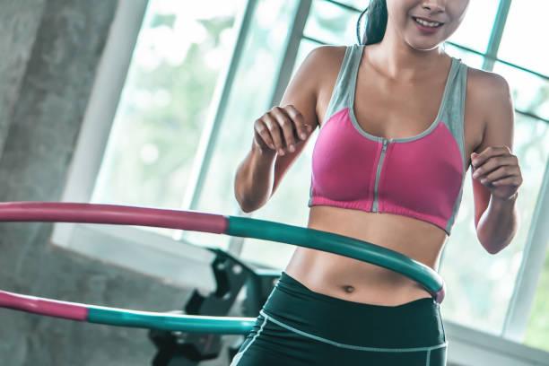 mujeres no reconocidas en ropa deportiva rosa está haciendo ejercicio con Hula hoop en el gimnasio para el concepto de estilo de vida saludable - foto de stock