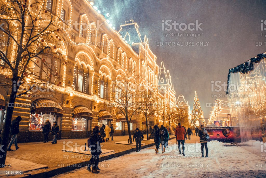 Unrecognized people preparing for Christmas and New year. New year and christmas market on Red Square in snowy Moscow. Tourists walk on the street/ stock photo