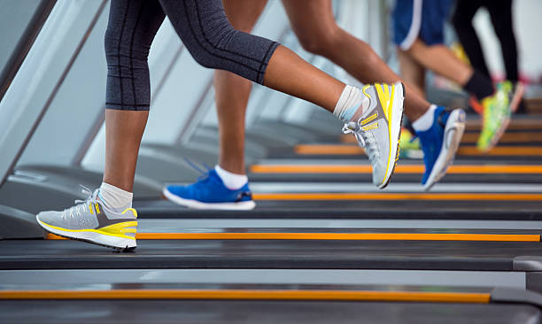 unrecognized people running on treadmill. - treadmill stock photos and pictures