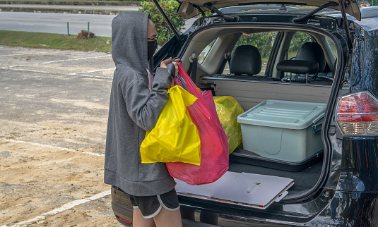 Photo of the unrecognized person wearing a jacket with hoodie and protection face mask, putting unused items in her vehicle for recycling station.