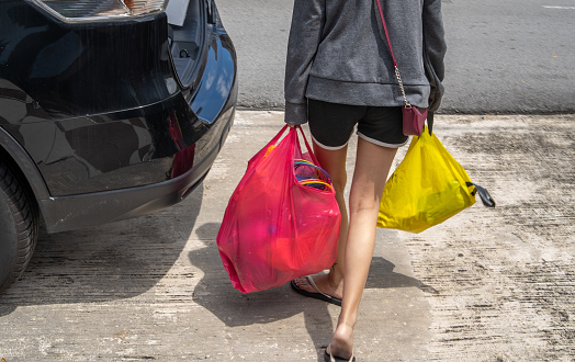 Cropped photo of unrecognized person taking two big plastic bag with recycling items to her vehicle. Recycling concept.
