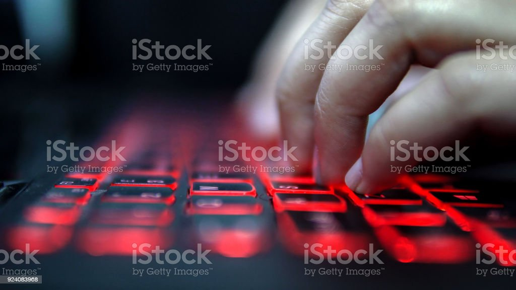 Unrecognized person typing on laptop computer red keyboard in dark, cinematic color graded footage stock photo