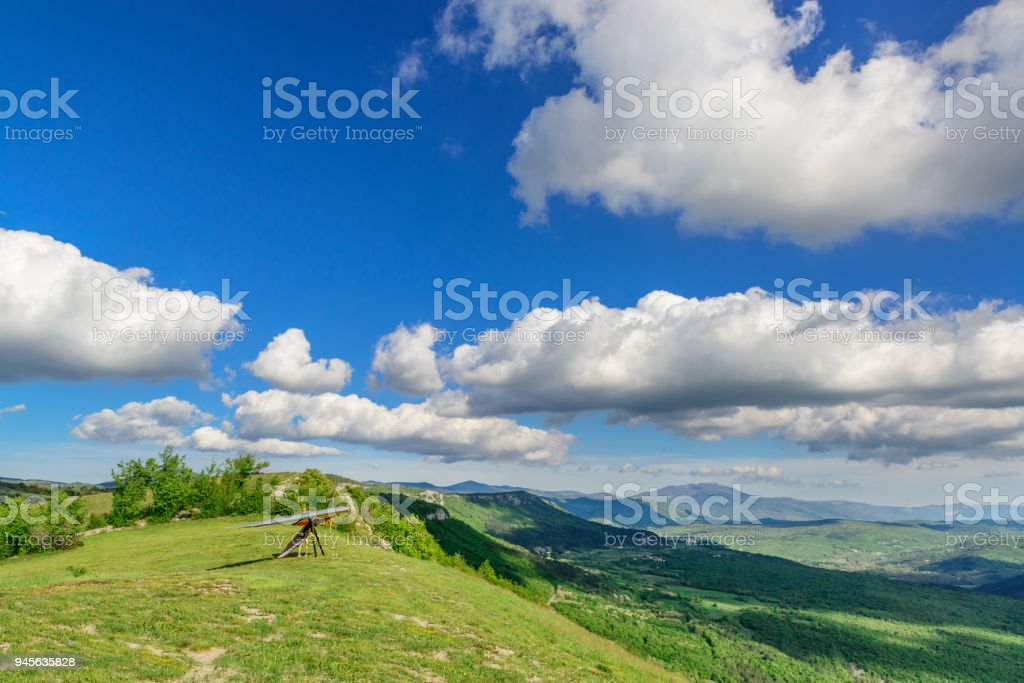 Unrecognized pilot stands ready to take off  with hang glider on a green grassy slope high in the mountains with blue sky and clouds above stock photo