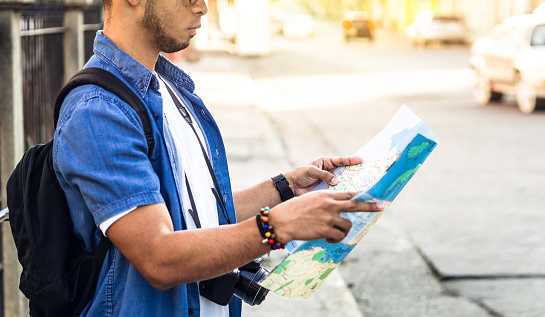 unrecognized Tourist man from behind looking at a map looking for a location. travel and tourism concept. copy space.