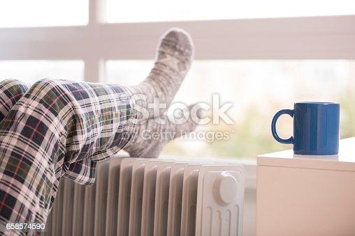 Unrecognized woman warming her legs on radiator in winter season. Woman wearing woolen socks, using heater, drinking coffee to relax in cold weather.