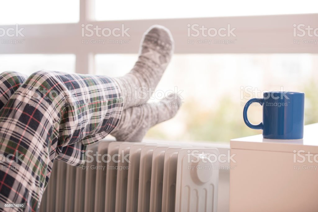 Unrecognized woman warming up her feet in winter. stock photo