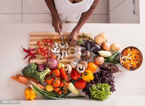 Photo from above of unrecognized women preparing fresh healthy salad using using various kind of vegetables .