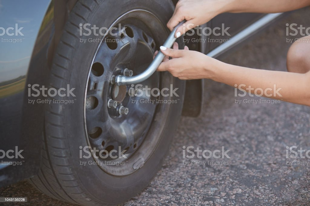 Unrecongnizable professional female mechanic going to change car wheel, uses special equipment, has damage with something. Cropped view of brocken car and woman solving problem. Repairing concept stock photo