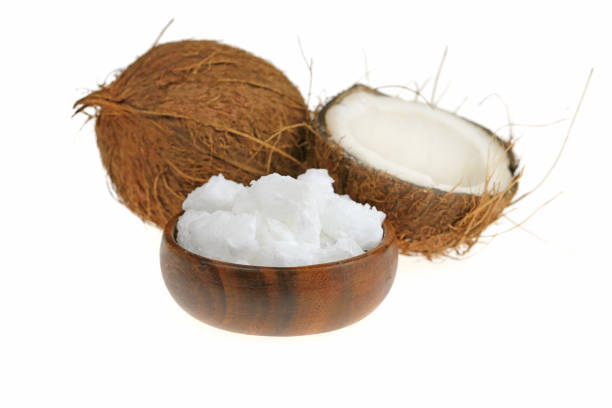 unrefined coconut oil. coconut in a cut and white natural coconut oil in a brown wooden round cup isolated on a white background stock photo