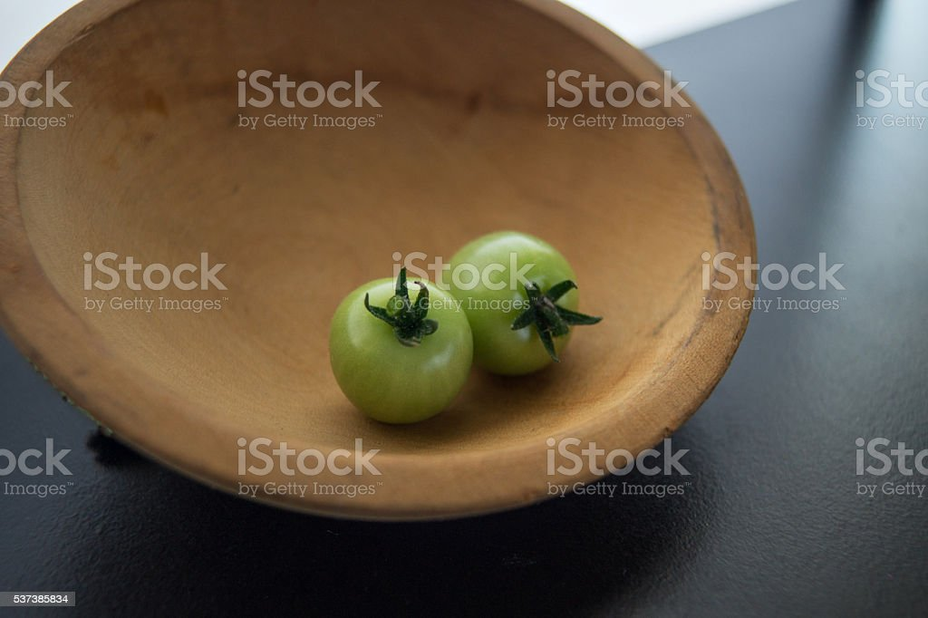 unripe cherry tomatoes - green - in wood bowl stock photo