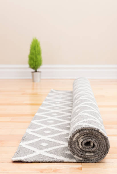 Unrolling carpet in a new home stock photo