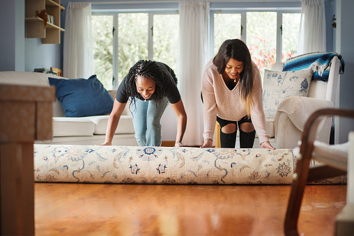 Shot of a two women unrolling carpet in new house