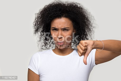 African woman in white t-shirt looking at camera contemptuously showing thumb down gesture symbol of negative feedback, bad quality evaluation and dislike, disagreement not recommend rejection concept