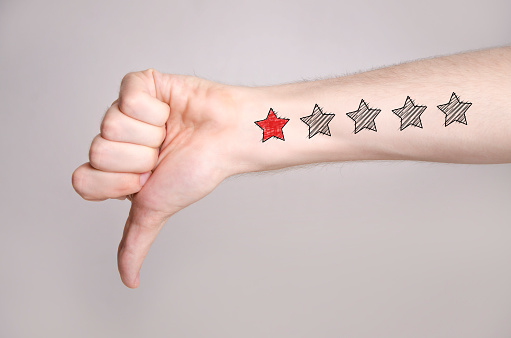 Closeup of man hand showing thumb down on gray background and one star rating on the arm skin. Dislike concept