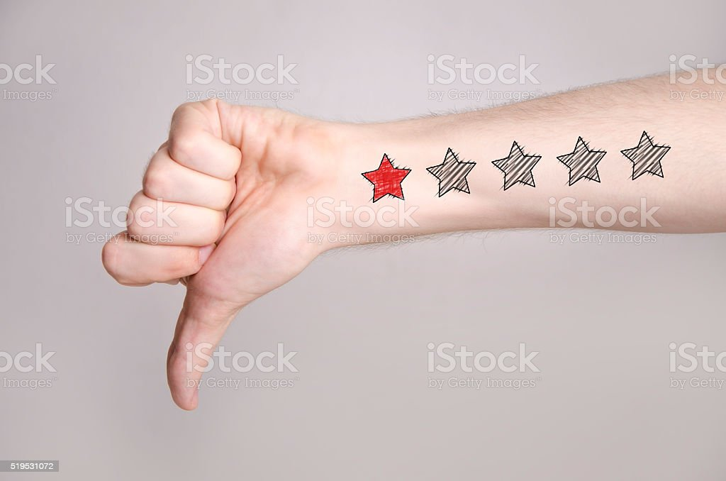 Unsatisfied custmer, thumb down, one star rating stock photo