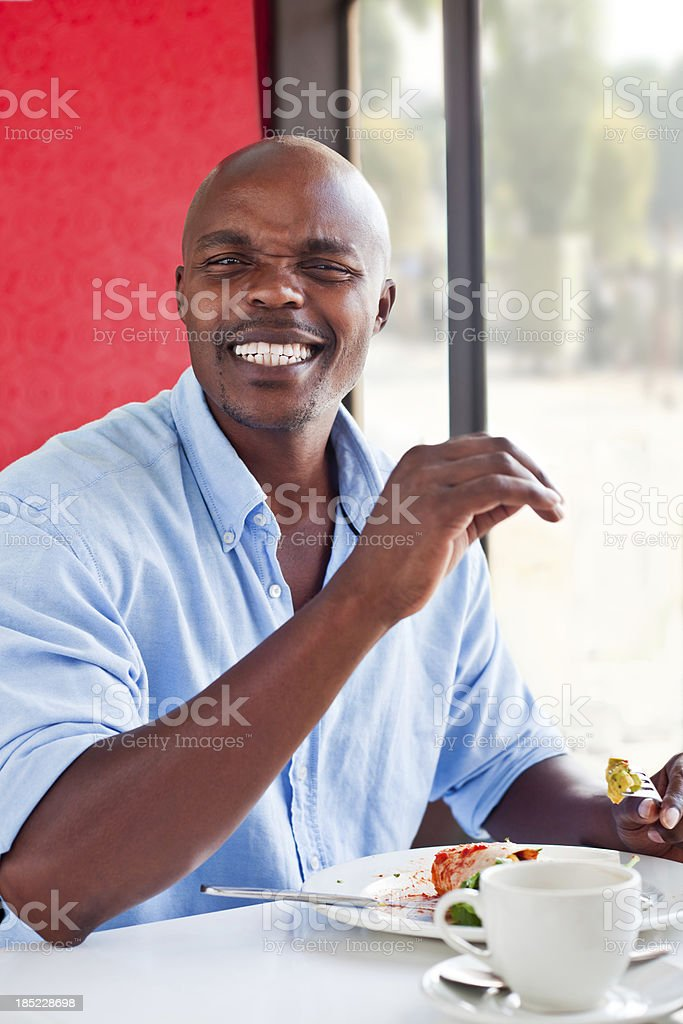 Unsatisfied customer A disappointed african man complaining about the food during lunch time. Adult Stock Photo