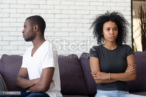 istock Unsatisfied married couple sitting separately on couch and not talking 1144680224
