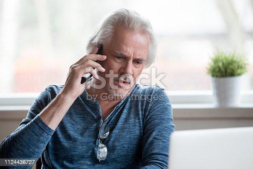 istock Unsatisfied senior man talking on mobile phone 1124436727