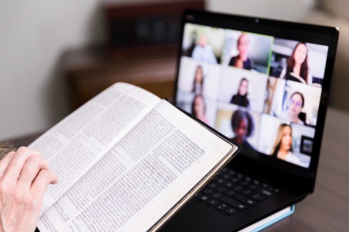 An unseen person joins her Bible study group through video.  They cannot meet because of coronavirus social distancing.