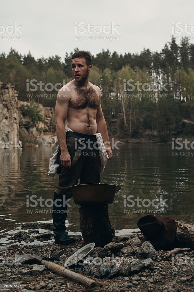 unshaved gold digger standing near lake with rocky bank stock photo