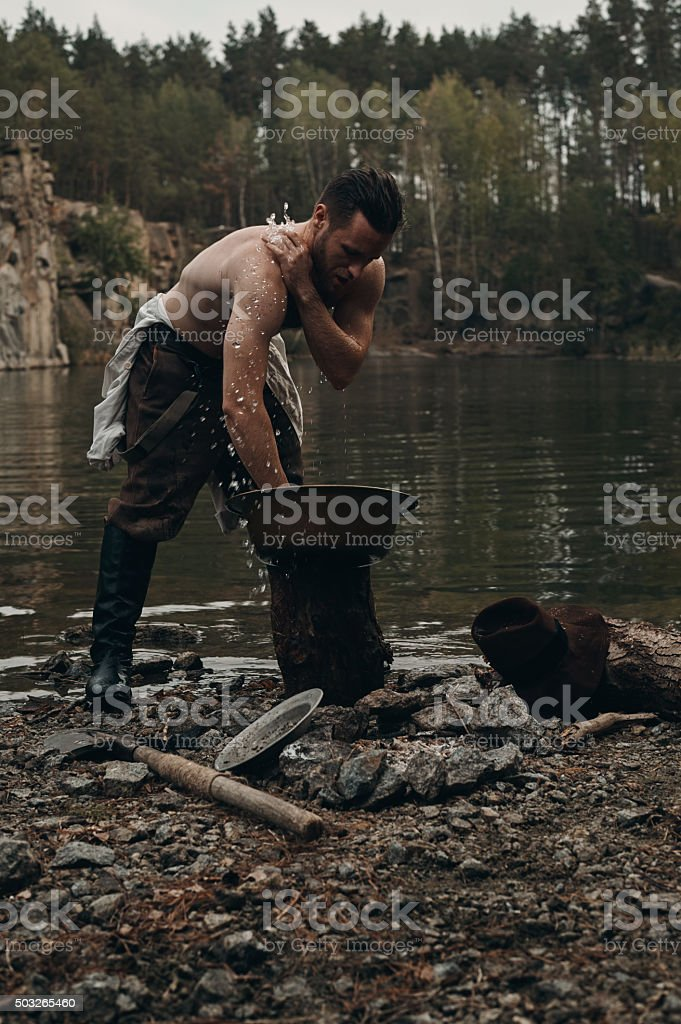 unshaved gold digger washes hands near lake with rocky bank stock photo