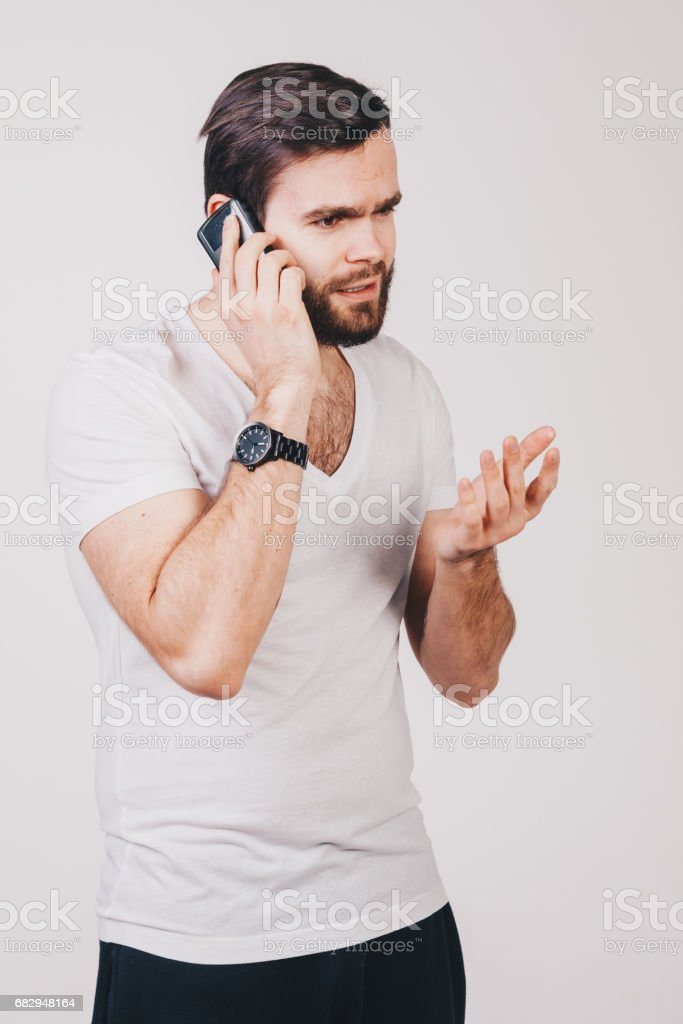 unshaved man in white t-shirt with tattoos talk on smartphone royalty-free stock photo