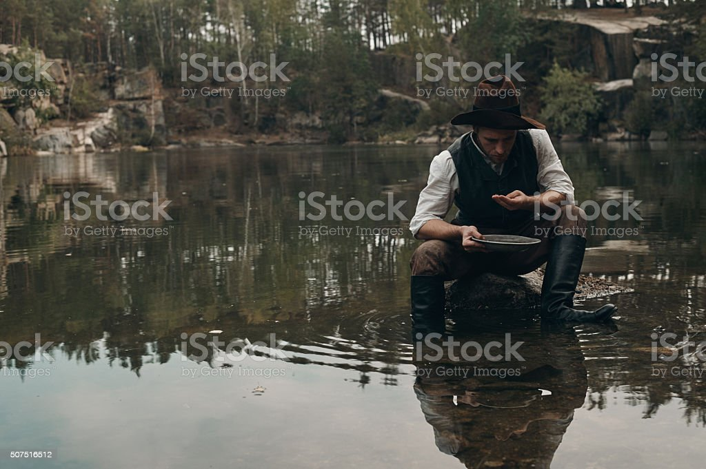 unshavedgold digger washes gold in the lake with rocky bank stock photo