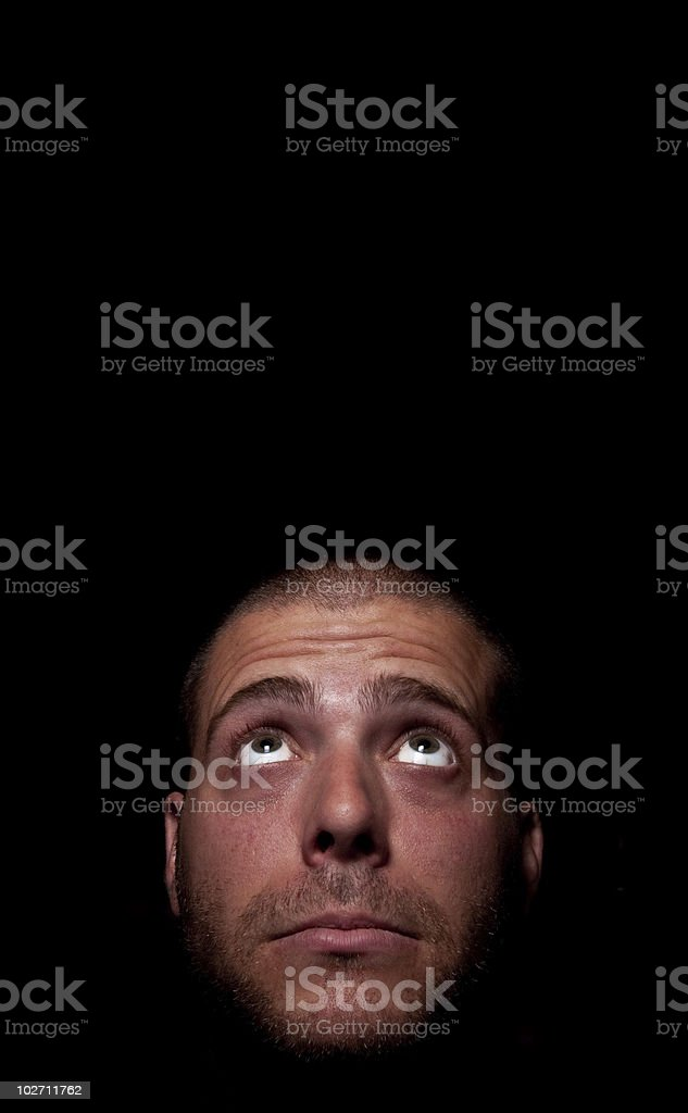 Unshaven man looking up into the dark. royalty-free stock photo