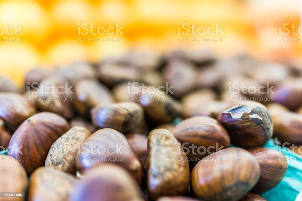 Unshelled chestnuts in shells on display at market stock photo