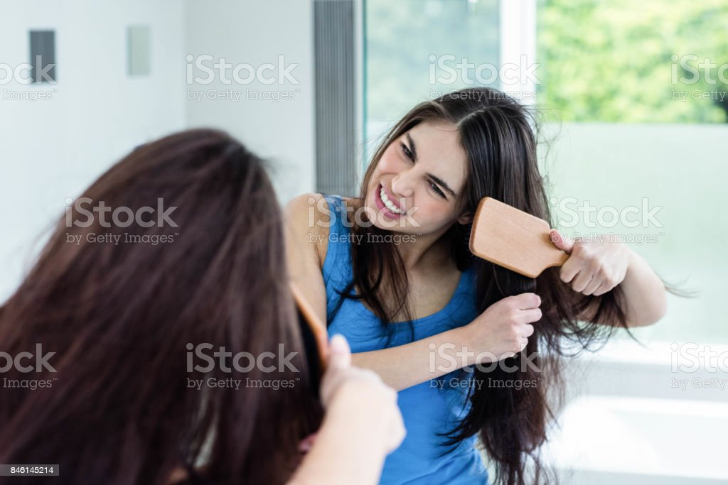 Unsmiling brunette combing stock photo