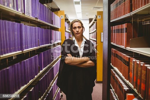 1070981872istockphoto Unsmiling lawyer standing between shelfs with arms crossed 538203013