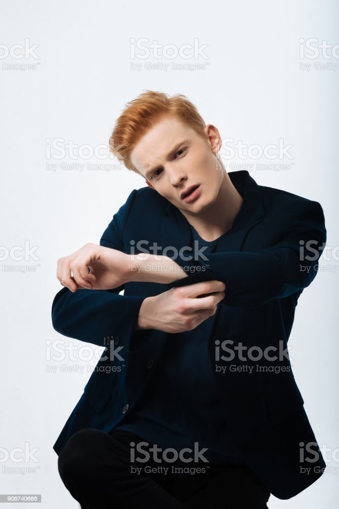 Unsmiling man buttoning up his sleeve stock photo