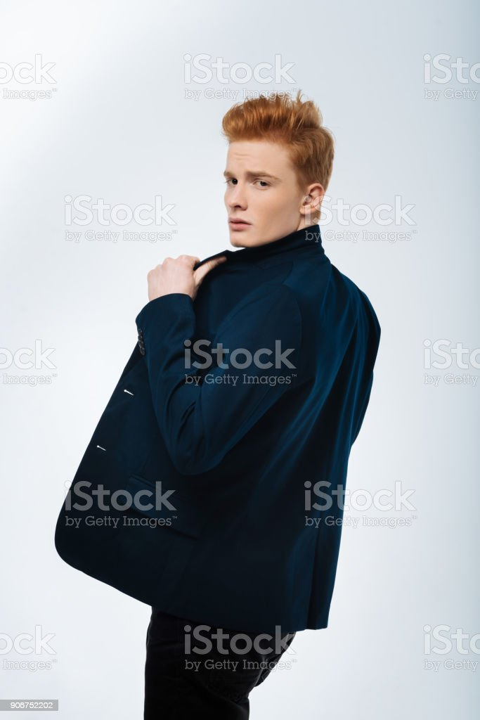 Unsmiling young man touching his jacket stock photo