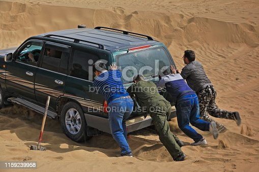 Keriya County, China-October 5, 2017: Car-pushing drivers unstuck a green off-road car for touristic service stuck in sand while driving through the treacherous loose dunes of the Taklamakan desert.