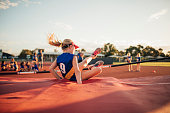 Little girl is landing on the mat after an unsuccesful high jump in athletics club.