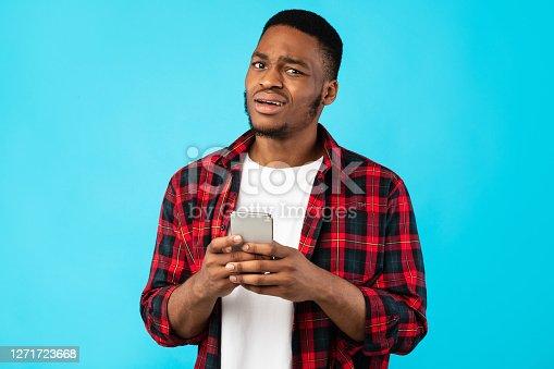 Unsure Black Man Holding Cellphone Posing Over Blue Studio Background. Unpleasant Call Concept
