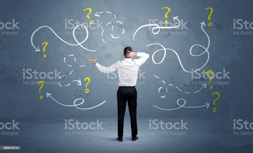 Unsure businessman with question marks stock photo
