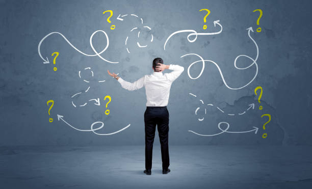 Unsure businessman with question marks A salesman in doubt can not find the solution to the problem concept with curvy lined arrows and question marks drawn on urban wall decisions stock pictures, royalty-free photos & images