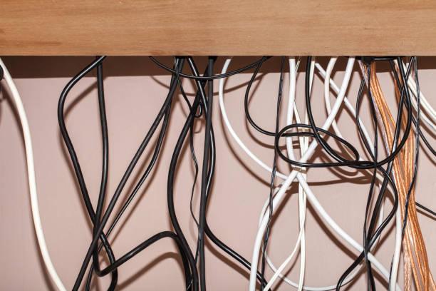 unordentliche kabel hängen hinter einem computerschreibtisch - kabelkanal weiß stock-fotos und bilder