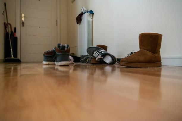 slordig hal met hardhouten vloer en veel schoenen - shoe stockfoto's en -beelden
