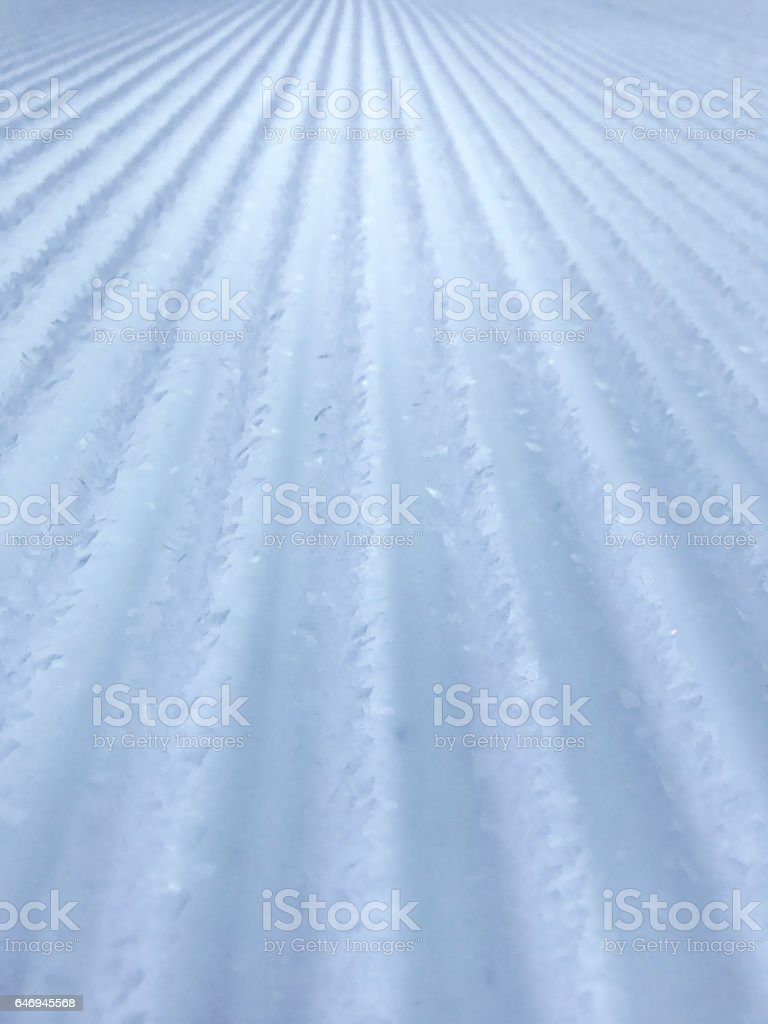 Untouched snow prepared ski piste giving perspective background stock photo