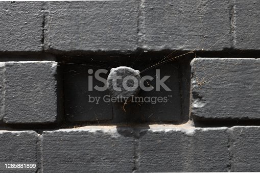 brick wall Capped pipe protruding from a gray.