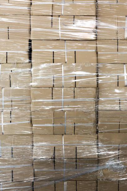 Boîtes de papier non utilisées empilées emballées par du plastique - Photo