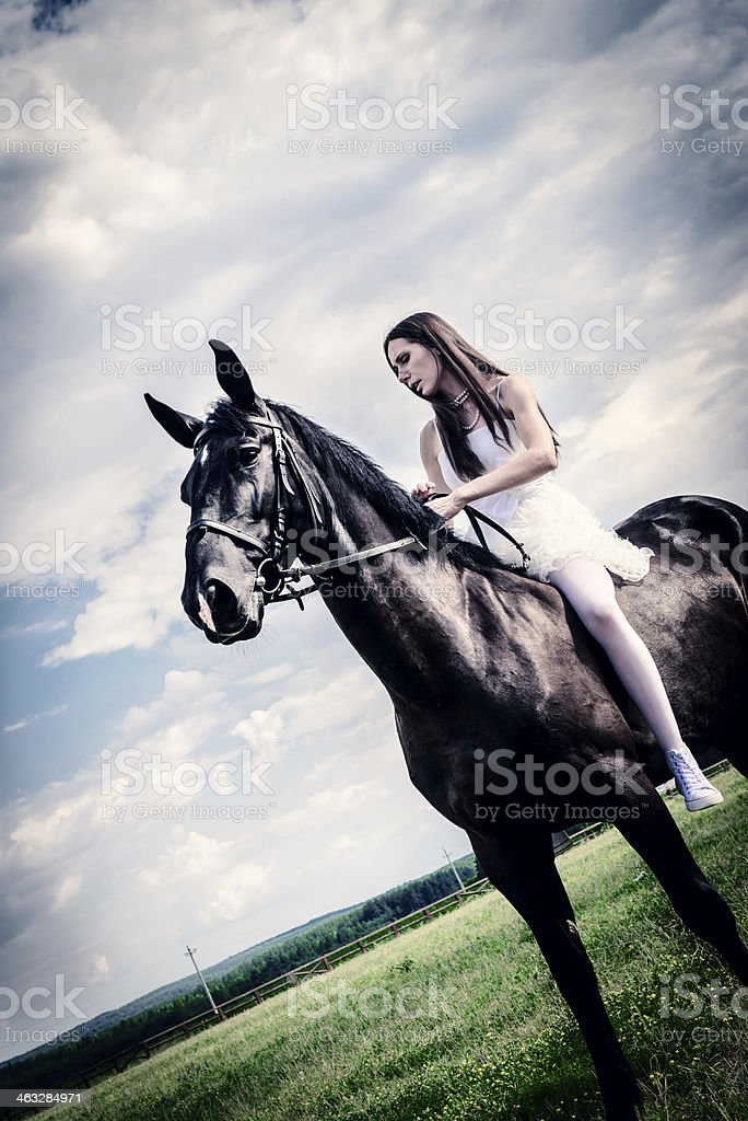 unusual bride at wedding on black horse outdoors royalty-free stock photo